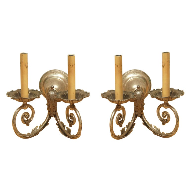 Pair of silver gilt two-arm wall sconces with leaf motif. Height includes candle shaft. Sconce height is 5.5