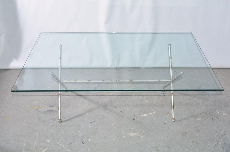 The contemporary coffee table is made of a glass top and faux bamboo metal
