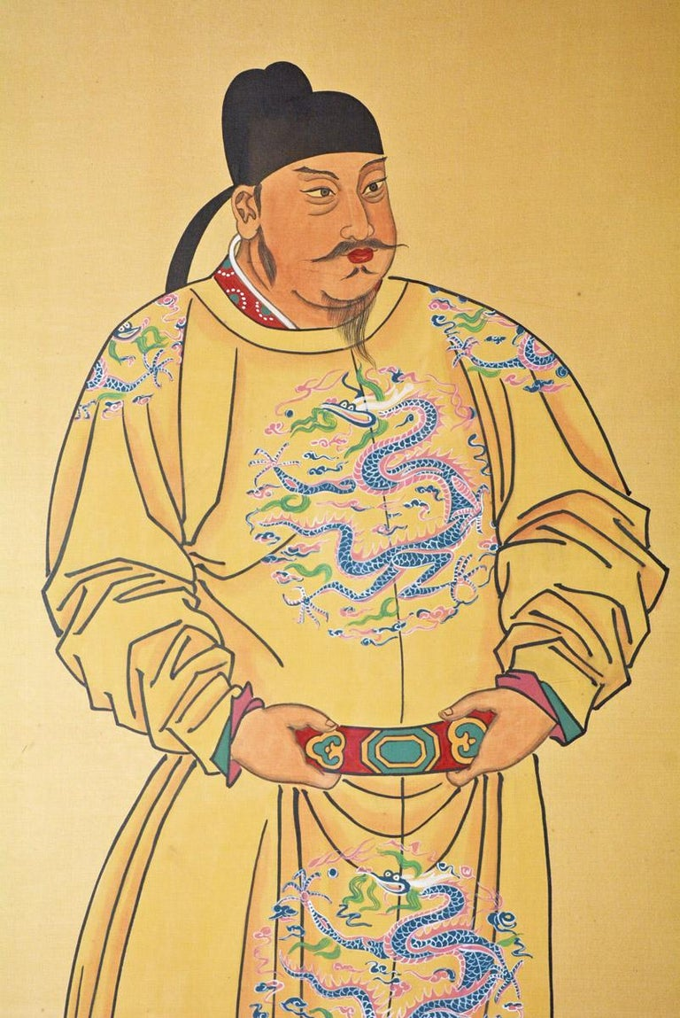 The black framed painting on silk (under glass) is of a distinguished Chinese gentleman who wears a yellow ceremonial robe embellished with blue and pink dragon-like figures on the skirt, blouse and shoulders. The print in matted with a