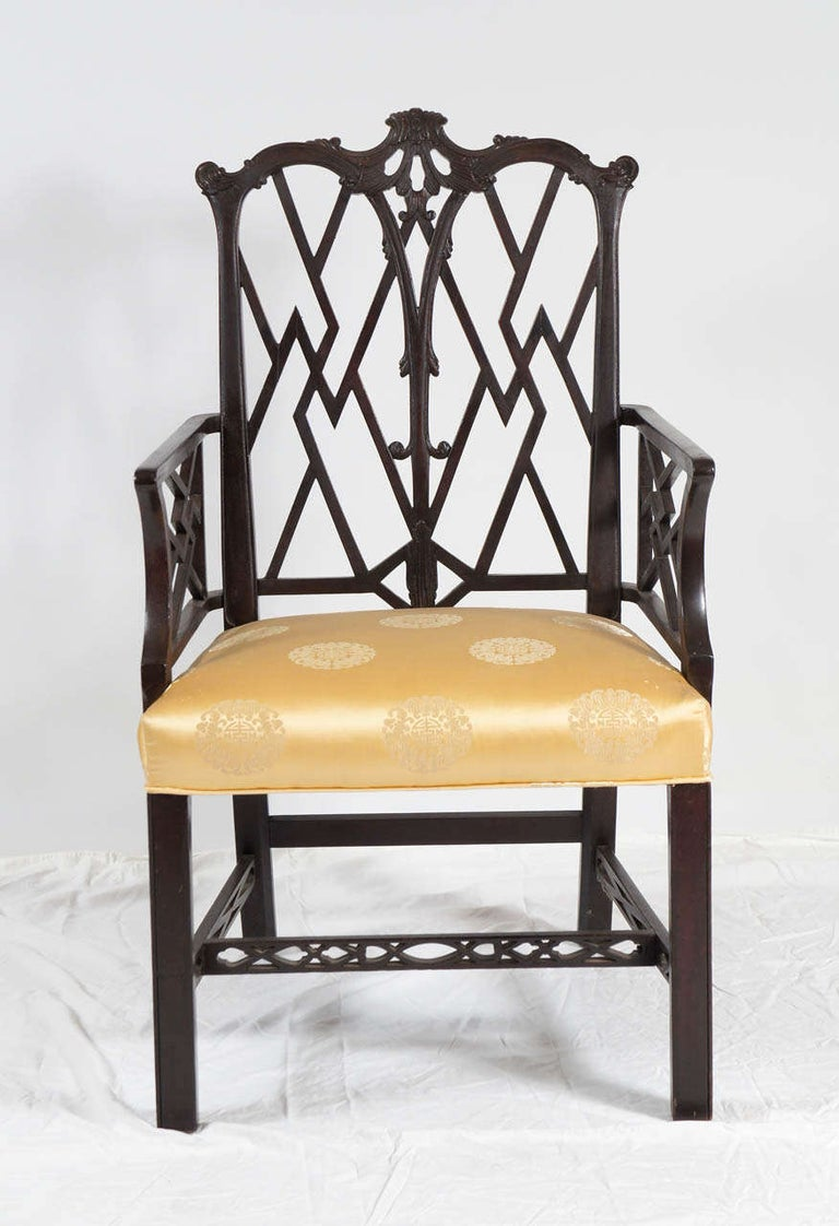 Chinese Chippendale-style armchair with elegant fretwork on back, arms and stretchers - and lots of pizzazz. Black lacquer wood and gold patterned satin upholstered seat. For extra seating in the living room or perfect as a desk chair.