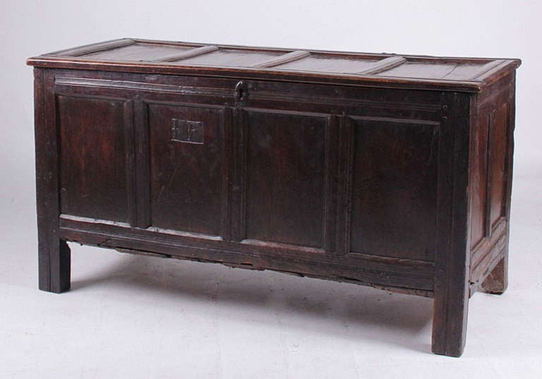 A paneled Jacobean cassone oak chest with straight legs, snipe hinges and the carved initials