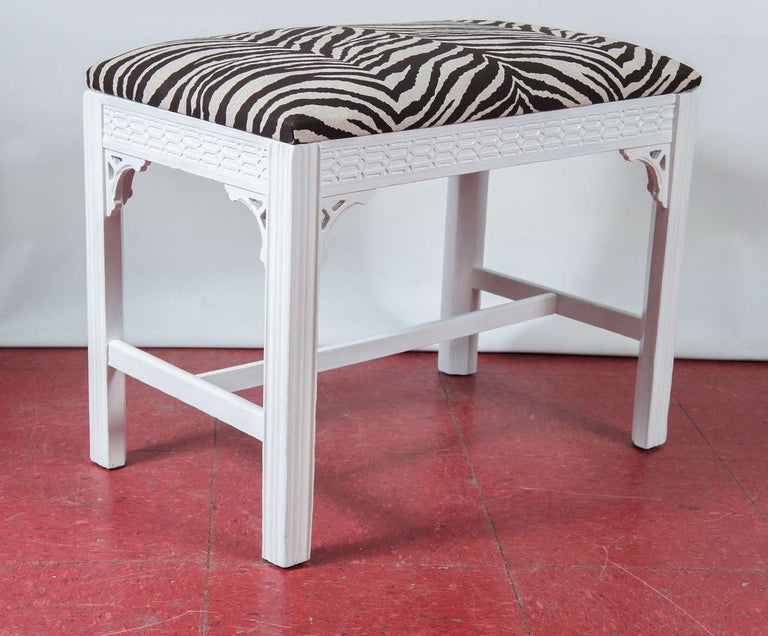 White painted bench or ottoman or stool with zebra linen upholstery, carved apron panels, decorative corner brackets and stretchers.