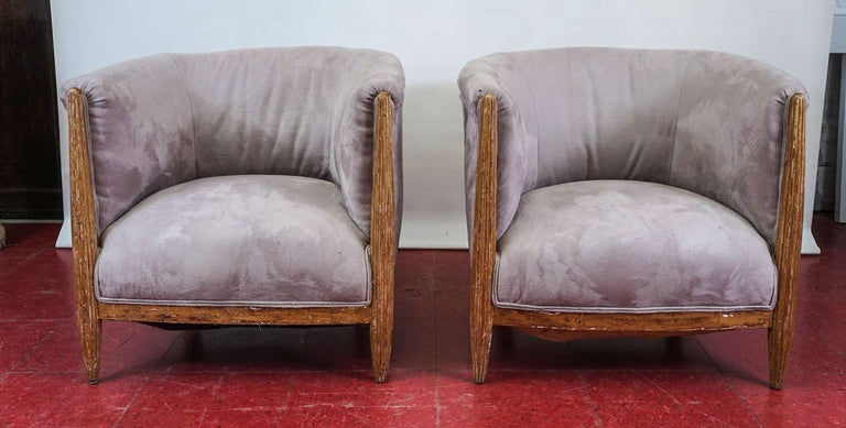 Unusual pair of French Art Deco armchairs with curved barrel backs and shaped fluted legs with rubbed gilt. The fabric is taupe/grey ultra suede.  Seat depth: 19