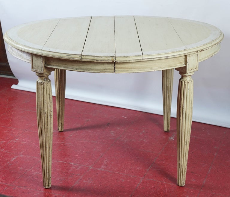 Gustation style painted cream with a greenish tint and a white boarder, the table has tapered fluted legs and is extendable. Leaves are not available. Excellent as a kitchen table.