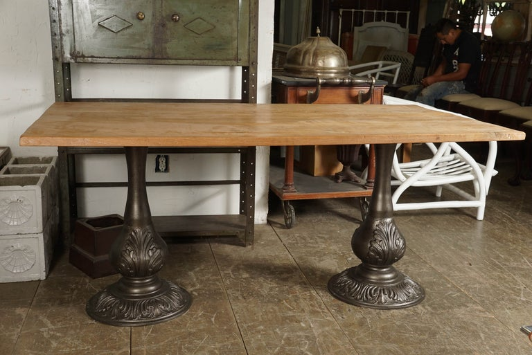 The top is composed of rustically smooth planks of teak wood, while the pair of pedestals are of antique silver cast iron. Each, decorated with acanthus leaves, has at the top four flanges with holes for securing the thick teak wood board. Top and
