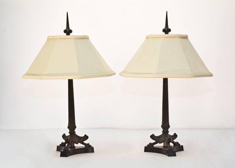 The pair of small classical Greco Roman-style lamps have column shafts set on three-legged and footed bases decorated with acanthus leaves and placed on platforms. The lamps are topped with bronzed spike finials. Each lamp, electrified for US use,