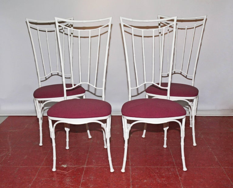The faux bamboo dining chairs are made of wrought iron painted white and have seats upholstered in purple outdoor fabric. Seats can be easily recovered with a fabric of your choice.