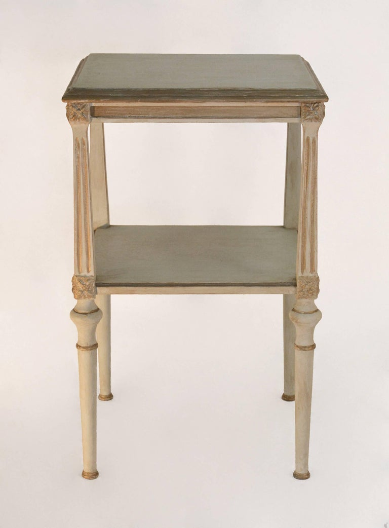 The vintage nightstand is painted light grey with gilt trim and has two shelves, fluted supports, decorative square rosettes and round legs. Great as end table night table or any area that you need a small stand. Suitable for Swedish Gustavian style