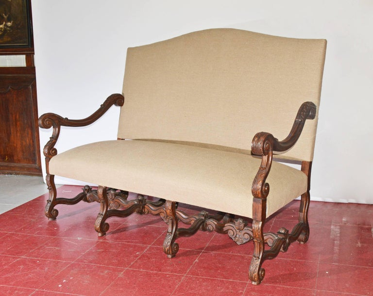 The Louis XV or Baroque Thorne style sofa or settee has hand-carved oak arms, legs and stretchers decorated with leaves and curling volutes. The newly applied upholstery is light brown linen. The seat is cushioned with padding and steel
