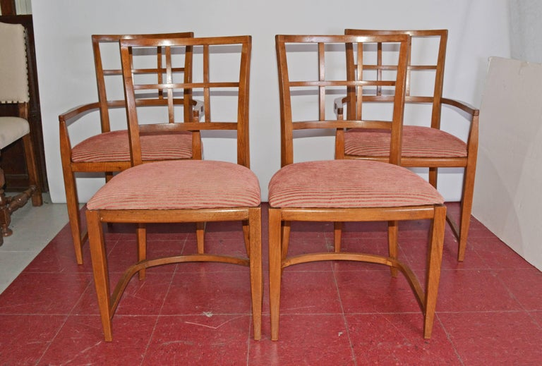The four Art Deco dining chairs, two arm and two side, have rounded leg framing and backs. The seats are newly upholstered in ribbed red and tan striping.