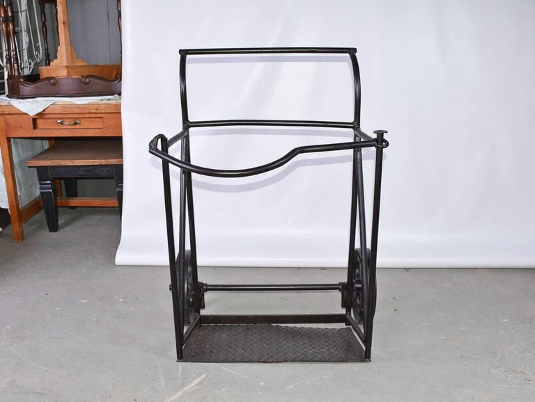 Vintage industrial black iron two-wheeled cart or hand truck, circa 1900. Top front bar unhooks at left side and swivels.