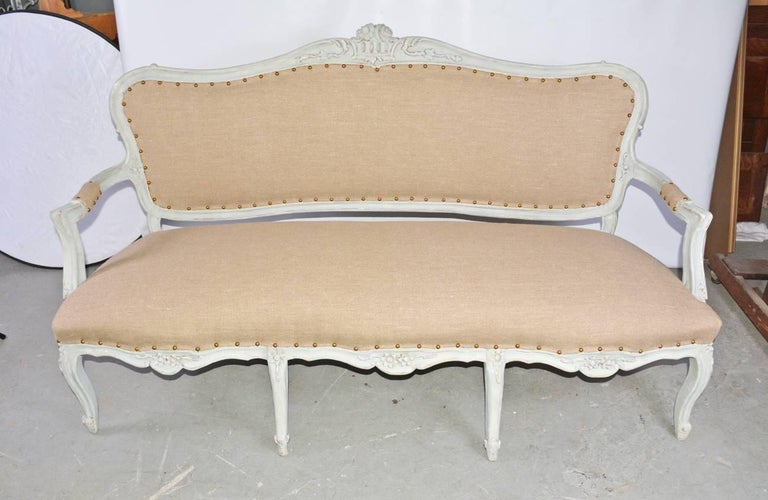 19th century French Louis XV style sofa or bench painted in a French blue-grey, with floral motives en relief. Newly reupholstered in a tan tight weave muslin. Measures: Arm height 25