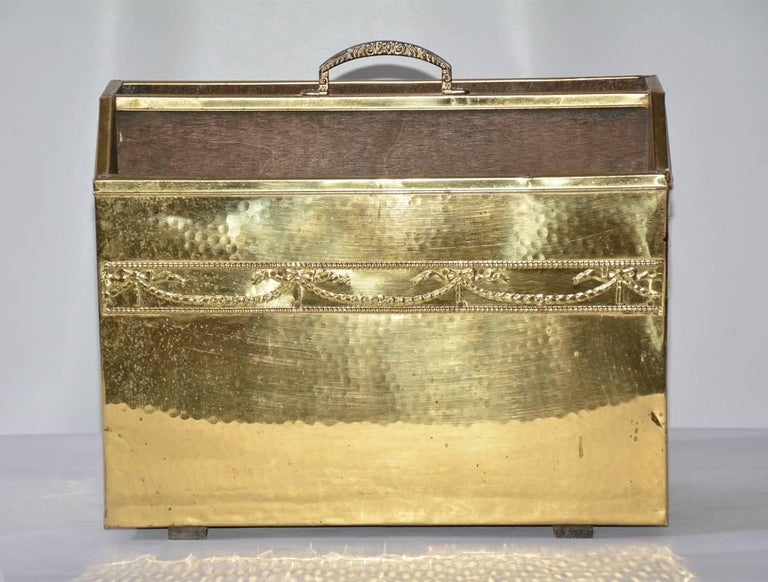 The vintage magazine basket is made of hammered brass sheeting on the front and sides nailed to a wood base with a brass handle top centre. A band of festooning and bows runs across the front. Wood runners are attached to the bottom.