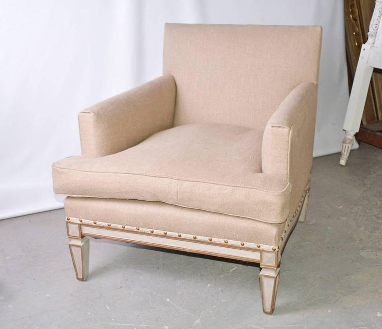 The vintage neoclassical armchair is newly upholstered in beige linen and has panelled legs and frame painted gold and white. Brass nailheads secure the upholstery. The seat is extra deep.