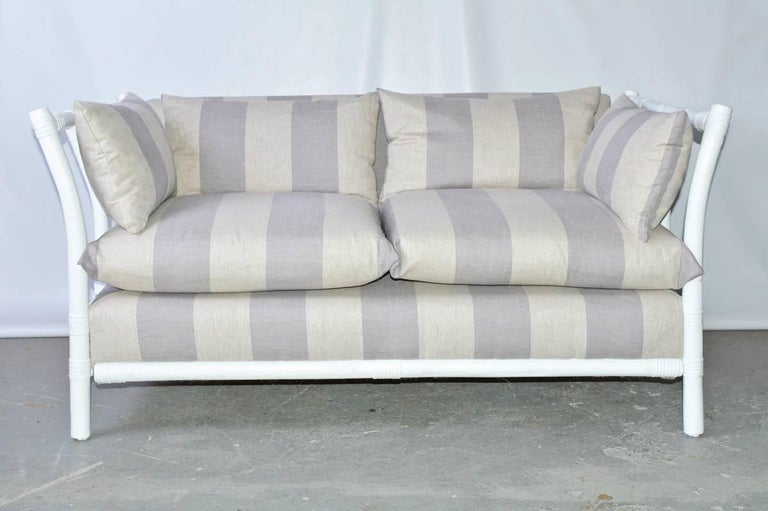 The faux bamboo or rattan love seat is designed for the enclosed porch or sun room. The raffia rapped poles are newly painted white and the new cushions are covered in beige and taupe striped line. Measures: Arm height 27