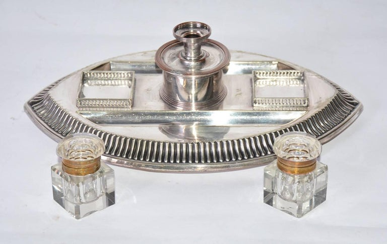 The antique silver-on-copper and crystal pen and ink desk set is composed a footed tray with two indentations for feathered pens or writing instruments, two lidded ink bottles with brass hinges attached to brass rims at the openings. There is a