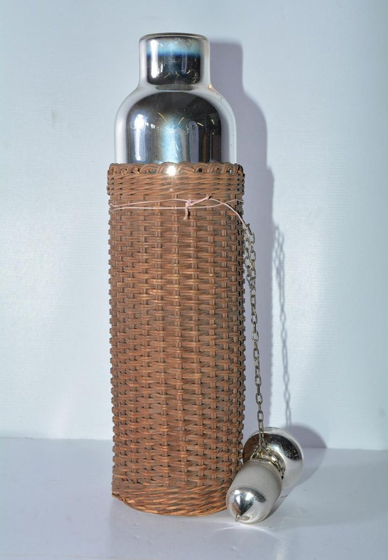 Unusual vintage mercury thermos with wicker outer layer.