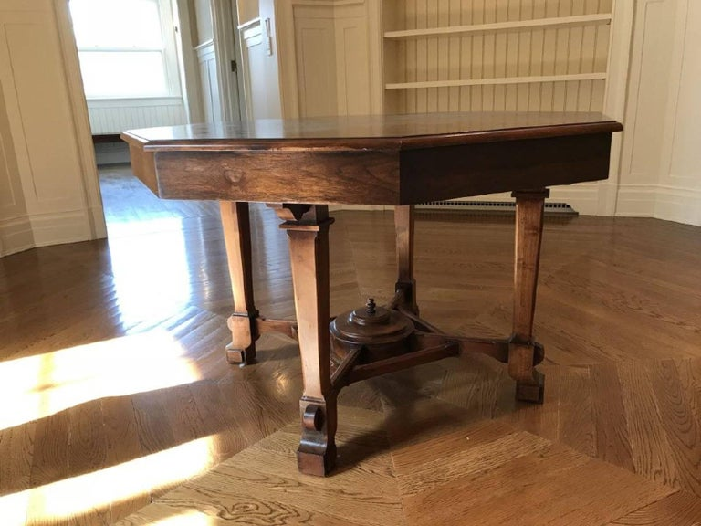English Regency Revival antique circa 1900 octagonal mahogany center, parlor or library (for reading or displaying books and magazines) table refinished in a mahogany tone. The table features a six-sided top with an apron, supported by four legs and