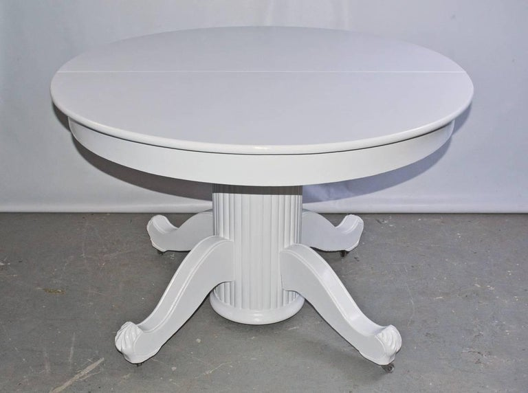 The Victorian round dining, breakfast or center table (library or hall) has a fluted pedestal leg with four splayed feet and attached casters. The table is painted glossy white.
