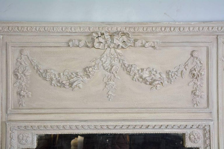The antique French trumeau mirror is in the Louis XVI neoclassical style. Across the top is an egg-and-dart cornice and a floral garland tied with a rippling bow. The mirror glass is framed by a beaded border and ribbon border. The frame is painted