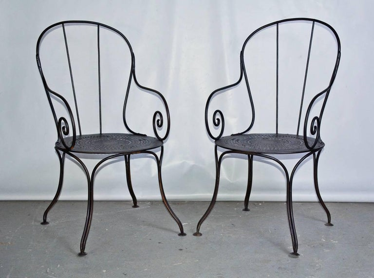 The pair of antique French outdoor public park or garden metal armchairs, made of wrought iron painted black with pierced pattern iron seats. Bistro style chairs. Think of them as stylish occasional chairs for the porch or patio.