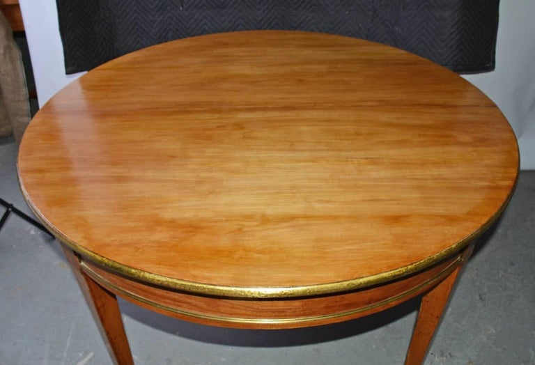 19th century fine circular dining table with all around brass trim and a thinner one on the lower edge of the skirt, tapered leg terminating in brass casters. Strong Viennese Biedermeier or Neo-Classical influence. The simplicity of design and light