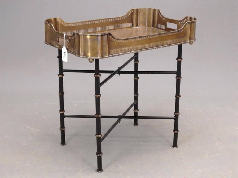 The vintage brass gallery tray coffee table or side table sits on crisscross table legs that collapse for easy storage. The tray has filigree sides and the metal legs are painted lacquer black with spaced gold rings imitating faux bamboo. The top of