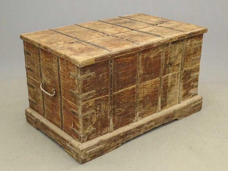 The antique handcrafted hardwood trunk or blanket chest is constructed with iron straps. Two-thirds of the top is hinged for opening. Wrought Iron handles are attached to the sides. Hand carved scroll-work is featured at the bottom center. The trunk