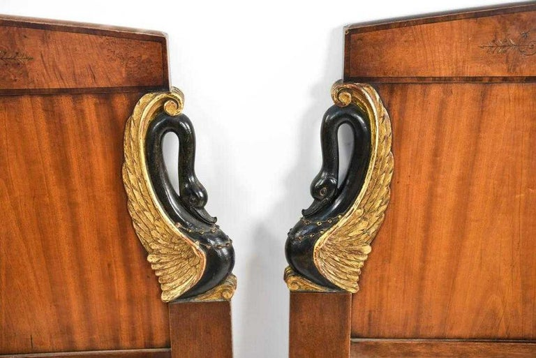 The pair of antique carved single headboards are in the Empire style. The carved black swans on either side have gilt wings, and painted cartouches are in the center. Condition: Loss to paint. Scratches, scuffs, wear consistent with age and use.