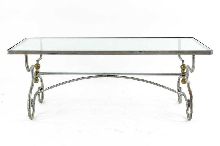 The contemporary Maison Jansen inspired wrought iron steel coffee table has a glass top inset in a frame. The two gracefully curved legs, embellished by pairs of brass knobs, are secured by two cross bars, one straight and one arched. The table