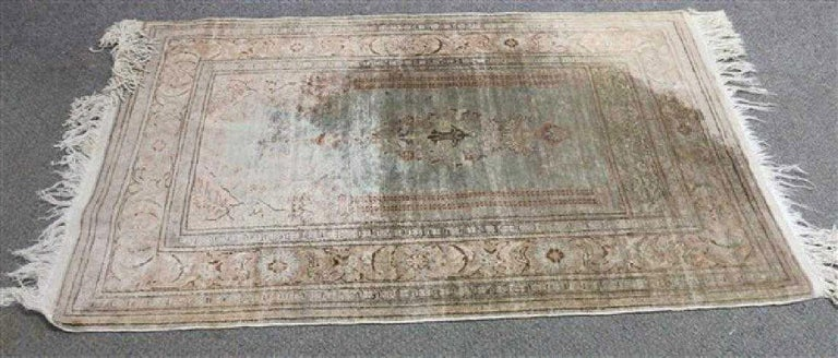 The antique wool scatter rug features a Mid-Eastern columned archway in the centre with a lantern and other motives. The border is arranged with stylized leaves and flowers. Predominant colors are blue, greens and browns.