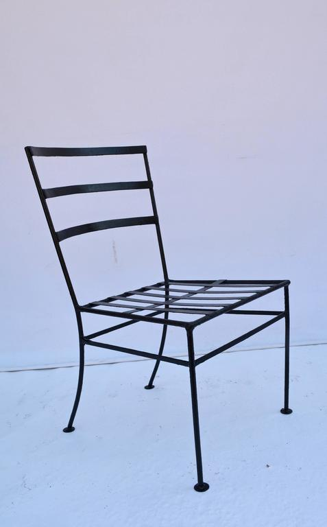 Vintage metal garden lounge or dining chairs are made of black wrought iron. One chair has arms and the other is armless. The cross-hatch seats are ready for the cushions of your choice.