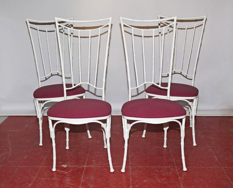 The faux bamboo dining chairs are made of wrought iron painted white and have seats upholstered in purple outdoor fabric. Seats can be easily recovered with a fabric of your choice. Please ask us about it.