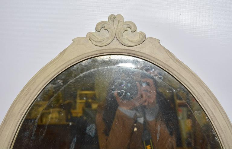 A fine oval frame mirror, painted light grey, is decorated at the top with two back-to-back scrolls. The silvered mirror is bevelled and the backing is wood and wired for hanging.
