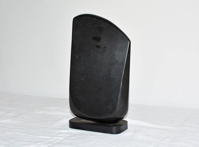 The contemporary black marble sculpture sits on a black wood base lined underneath with green felt. Award winning sculptor, Jean Downey (1931-2009) born in Canada, studied art in Illinois, New York and Connecticut. Her work is included in private