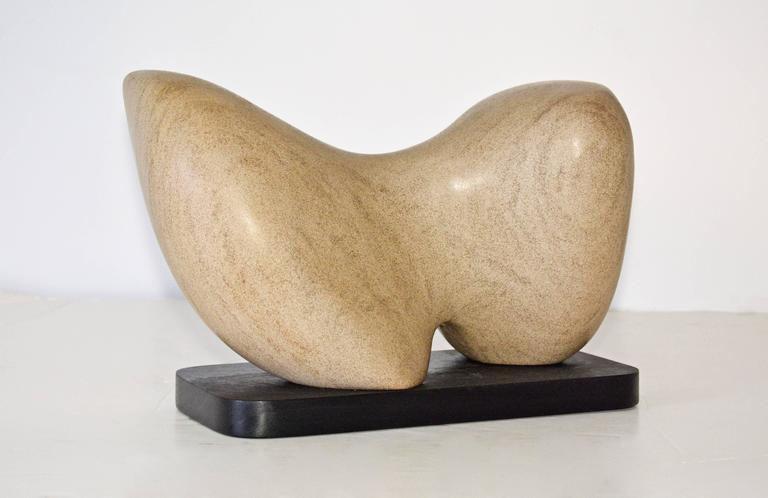 Award winning sculptor Jean Downey (1931-2009). The contemporary brown marble sculpture sits on a black wood base. Jean Downey was born in Canada, studied art in Illinois, New York and Connecticut. Her work is included in private and corporate