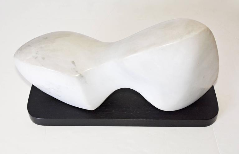 The contemporary white veined marble sculpture sits on a black wood base. Sculptor is Jean Downey, (1931-2009). She was born in Canada, studied art in Illinois, New York and Connecticut. Her work is included in private and corporate collections in
