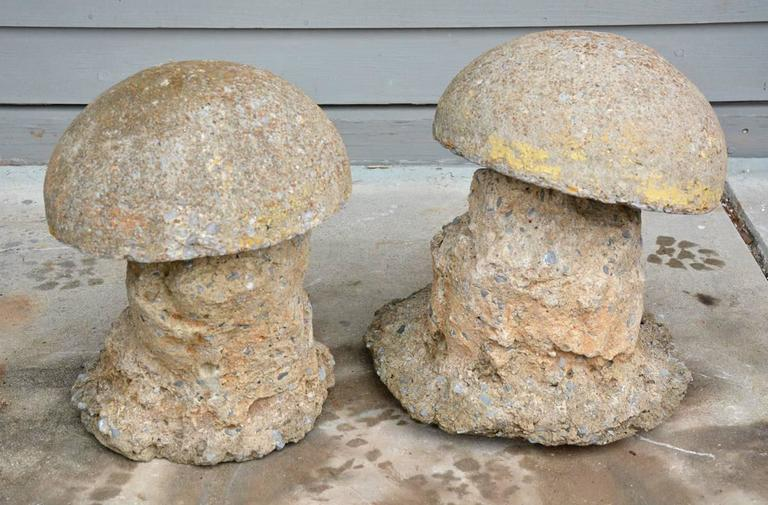 Charming pair of antique mushroom garden ornaments have separate tops and bottoms. They are made of molded cement. The tops have iron bars underneath that fit into holes of the bottoms.  The dimensions are for the larger mushroom.
