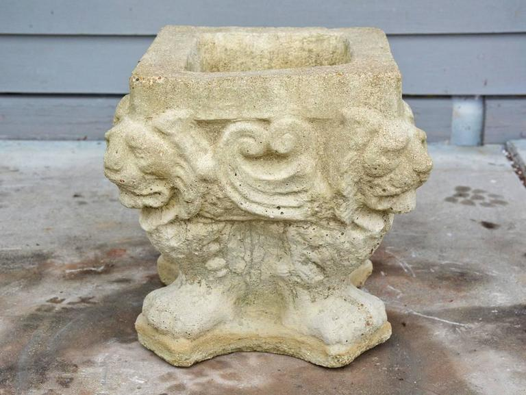 The square antique garden jardinière made of stone is embellished with four lion's heads and feet. Wonderful garden element.   Top measurement: 10.75