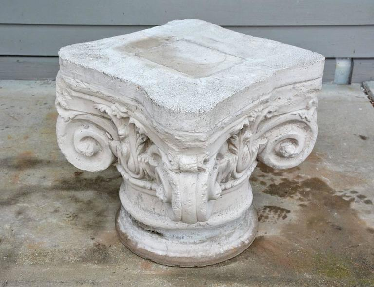 The ionic cast stone cement pedestal has the classic curls at all four corners based on the ancient Greek inspiration of ram's horns. Leaves embellish the design as well. Makes a great low garden, patio, porch side table or base.