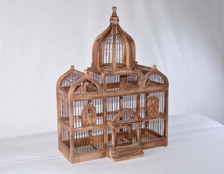 The antique architectural bird cage has a pair of peaked roofs and tall center dome under which is a pedimented portico leading to a swinging door. The frame is wood painted brown and is interspersed with wire caging. To the left at the bottom is a