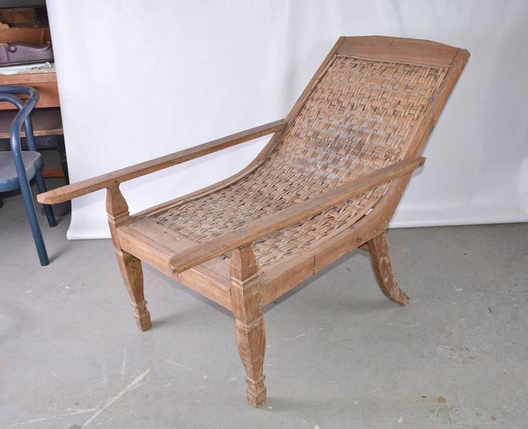 Indoor or outdoor British Colonial teak plantation or planters chair with cane seat and back. Wonderful weathered wood patina.