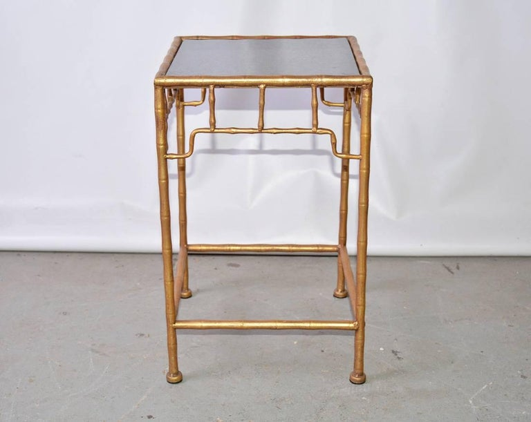 The vintage faux-bamboo occasional table in the Chinese style is composed of gilt metal and an inset black polished marble top. Great as a side or plant table.