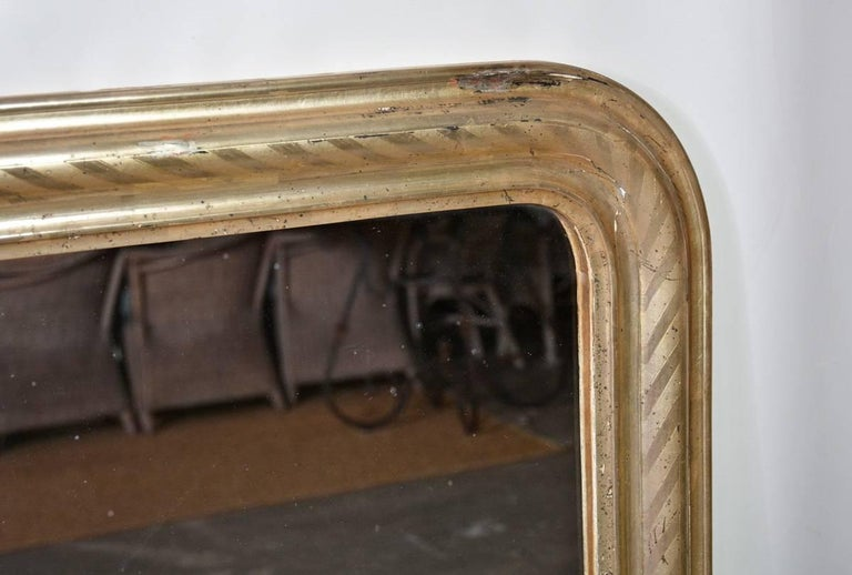 19th century French Louis Philippe mirror has a wide frame painted with silver gilt with a spiral pattern and has wood panels across the back. Ready to hang.