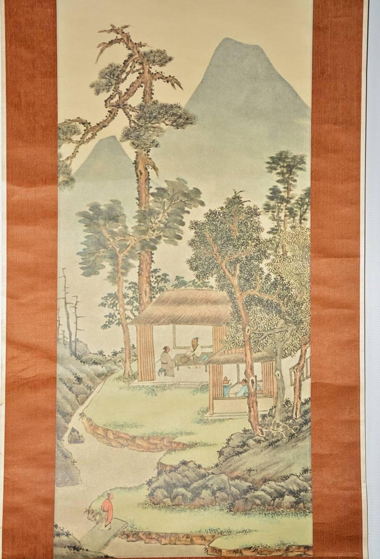 The Chinese hand-painted decorative wall panel made of paper features a landscape with figures, buildings, trees and mountains and fine calligraphy in several colors. The background of the panel has a light brown silky texture and is attached to