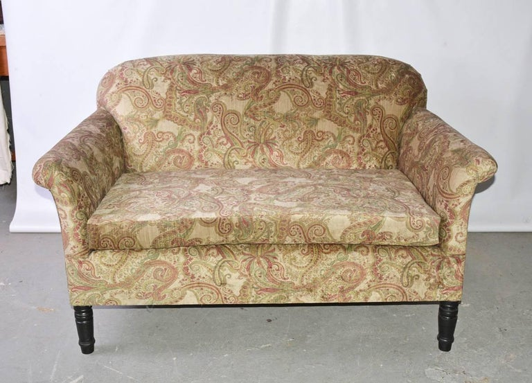 The vintage French Napoleon III-style loveseat is newly covered in cotton velvet, the pattern of which is a green and red paisley. The legs are stained black wood and the front ones are turned.  Arm height: 24.50