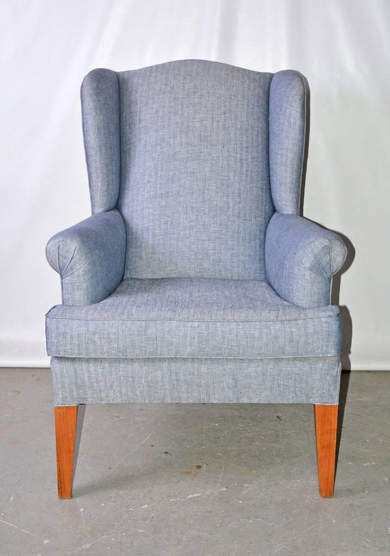 The vintage wing back armchairhas been newly upholstered in blue herringbone cotton. The legs are made of tapered blond wood.  Arm height: 25.50