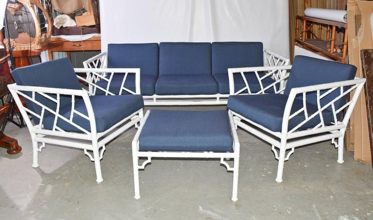 The four-piece indoor or outdoor vintage faux bamboo patio, garden or porch set has two armchairs, a three-seat sofa and a stool. The pieces are made of metal painted white. The cushions are upholstered with a blue zippered fabric. Under the seat