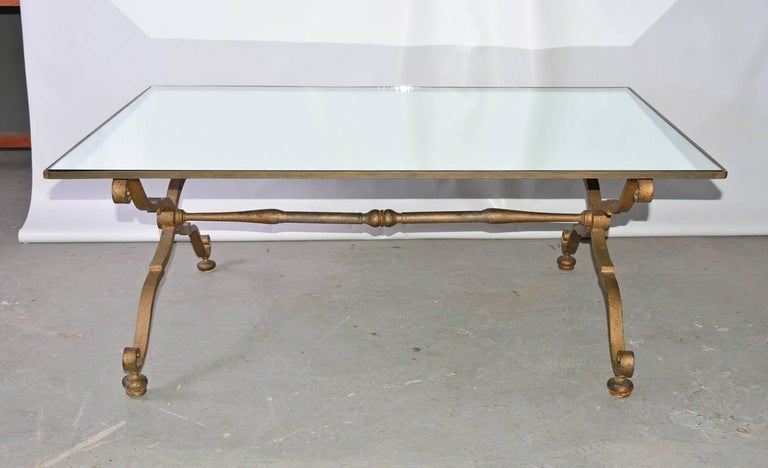 The glamorous rectangular Gilbert Poillerat style, circa 1940s vintage coffee cocktail table has Rococo gilt wrought iron criss-cross braces for legs attached to a stretcher. The top is a mirror set into a gilt wrought iron frame.