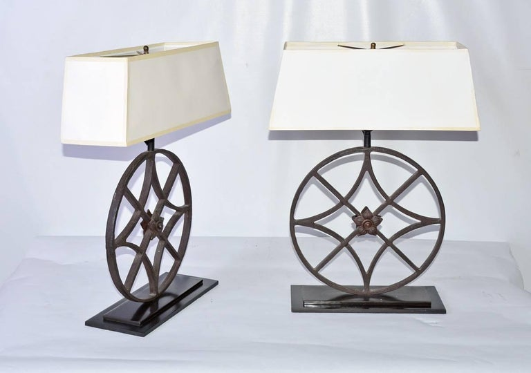 The pair of black wrought iron lamps are circular architectural elements fitted with centered rosettes. The elements sit on stepped bases of polished iron. Electrically wired for US use. The rectangular shades are made of white translucent plastic.